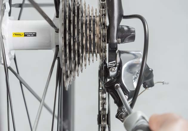 Ubica el destornillador sobre el H y aprieta hasta que alcances un alineación de la roldana superior con la corona. Imagen: ciclismoafondo